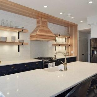 他の地域の中サイズのカントリー風おしゃれなキッチン (アンダーカウンターシンク、落し込みパネル扉のキャビネット、青いキャビネット、人工大理石カウンター、白いキッチンパネル、サブウェイタイルのキッチンパネル、シルバーの調理設備、淡色無垢フローリング、茶色い床、白いキッチンカウンター) の写真