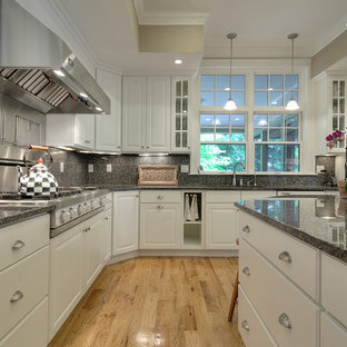 Large arts and crafts u-shaped eat-in kitchen in Portland Maine with an integrated sink, raised-panel cabinets, yellow cabinets, granite benchtops, grey splashback, stone tile splashback, stainless steel appliances, slate floors and with island.