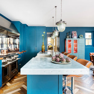 Свежая идея для дизайна: угловая кухня среднего размера в стиле фьюжн с раковиной в стиле кантри, фасадами в стиле шейкер, синими фасадами, столешницей из цинка, фартуком из зеркальной плитки, техникой из нержавеющей стали, островом, серой столешницей, обеденным столом, паркетным полом среднего тона и коричневым полом - отличное фото интерьера