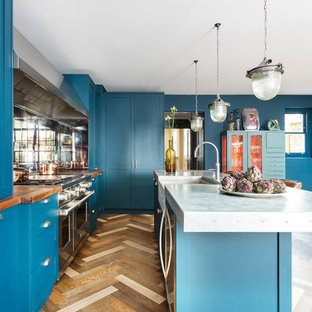 Mid-sized eclectic l-shaped open plan kitchen in London with a farmhouse sink, shaker cabinets, blue cabinets, zinc benchtops, mirror splashback, stainless steel appliances, dark hardwood floors, with island, multi-coloured floor and grey benchtop.