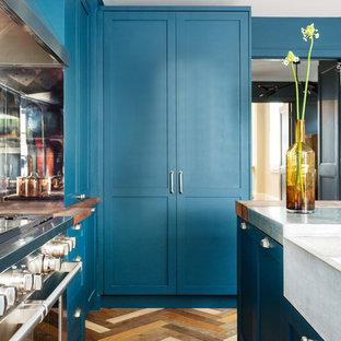 ロンドンの中サイズのエクレクティックスタイルのおしゃれなキッチン (エプロンフロントシンク、シェーカースタイル扉のキャビネット、青いキャビネット、亜鉛製カウンター、ミラータイルのキッチンパネル、シルバーの調理設備の、濃色無垢フローリング、マルチカラーの床、グレーのキッチンカウンター) の写真