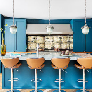 This is an example of a mid-sized eclectic l-shaped open plan kitchen in London with a farmhouse sink, shaker cabinets, blue cabinets, zinc benchtops, mirror splashback, stainless steel appliances, dark hardwood floors, with island, multi-coloured floor and grey benchtop.