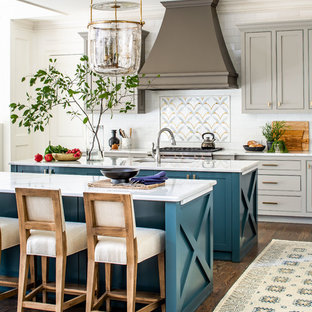 Country galley eat-in kitchen in Atlanta with an undermount sink, recessed-panel cabinets, turquoise cabinets, white splashback, subway tile splashback, stainless steel appliances, medium hardwood floors, multiple islands, brown floor and white benchtop.