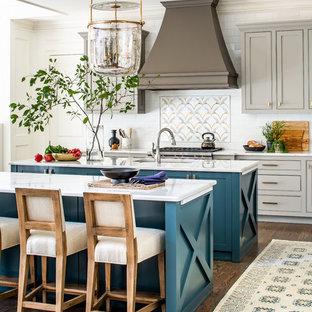 Zweizeilige Country Wohnküche mit Unterbauwaschbecken, Schrankfronten mit vertiefter Füllung, türkisfarbenen Schränken, Küchenrückwand in Weiß, Rückwand aus Metrofliesen, Küchengeräten aus Edelstahl, braunem Holzboden, zwei Kücheninseln, braunem Boden und weißer Arbeitsplatte in Atlanta