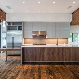 ヒューストンの大きいコンテンポラリースタイルのおしゃれなキッチン (シングルシンク、フラットパネル扉のキャビネット、グレーのキャビネット、人工大理石カウンター、茶色いキッチンパネル、ガラスタイルのキッチンパネル、シルバーの調理設備の、無垢フローリング) の写真