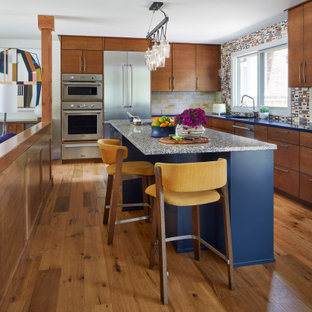 This is an example of a midcentury l-shaped open plan kitchen in Denver with flat-panel cabinets, medium wood cabinets, multi-coloured splashback, stainless steel appliances, light hardwood floors, with island and blue benchtop.