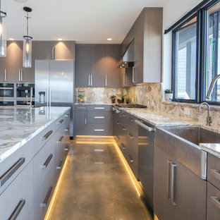 Inspiration for a contemporary l-shaped kitchen in Seattle with a belfast sink, flat-panel cabinets, grey cabinets, stainless steel appliances, concrete flooring, an island, grey floors, beige worktops and quartz worktops.