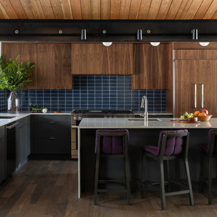 Inspiration for a midcentury l-shaped kitchen in Seattle with an undermount sink, flat-panel cabinets, dark wood cabinets, blue splashback, subway tile splashback, panelled appliances, dark hardwood floors, with island, brown floor and white benchtop.