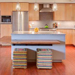 Idéer för ett modernt kök med öppen planlösning, med släta luckor, skåp i ljust trä, grått stänkskydd och rostfria vitvaror