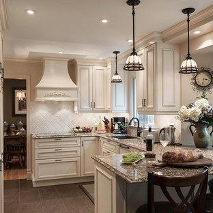 Foto di una cucina vittoriana di medie dimensioni con lavello a doppia vasca, ante a filo, ante bianche, top in granito, paraspruzzi beige, paraspruzzi con piastrelle in pietra, elettrodomestici da incasso, pavimento in ardesia, penisola e pavimento grigio