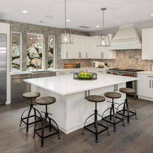 シアトルの大きいコンテンポラリースタイルのおしゃれなキッチン (エプロンフロントシンク、フラットパネル扉のキャビネット、白いキャビネット、マルチカラーのキッチンパネル、レンガのキッチンパネル、シルバーの調理設備の、無垢フローリング、茶色い床、白いキッチンカウンター) の写真