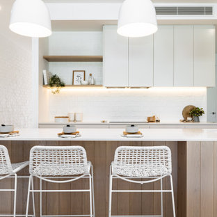 This is an example of a beach style galley kitchen in Sydney with an undermount sink, flat-panel cabinets, white cabinets, white splashback, white benchtop and with island.