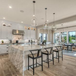 Geräumige Klassische Wohnküche mit Unterbauwaschbecken, weißen Schränken, Küchengeräten aus Edelstahl, hellem Holzboden, Kücheninsel, grauer Arbeitsplatte, Schrankfronten im Shaker-Stil, bunter Rückwand und Rückwand aus Stein in Seattle