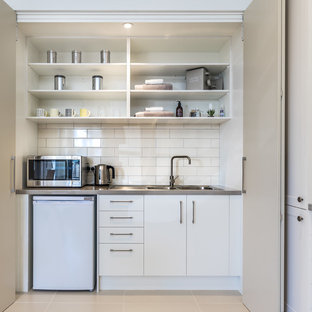 Photo of a small contemporary single-wall enclosed kitchen in Sydney with a double-bowl sink, flat-panel cabinets, white cabinets, granite worktops, white splashback, metro tiled splashback, white appliances and no island.