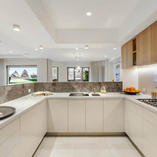 Inspiration for a mid-sized contemporary u-shaped open plan kitchen in Sydney with an undermount sink, flat-panel cabinets, limestone benchtops, white splashback, black appliances, ceramic floors, white floor, recessed, white cabinets, a peninsula and white benchtop.