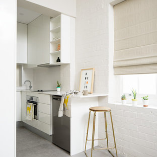 Photo of a small contemporary kitchen in Brisbane with white cabinets, stainless steel appliances, flat-panel cabinets, white splashback, glass sheet splashback and concrete floors.