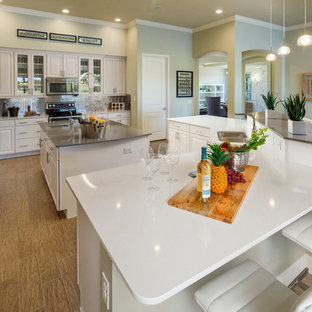 Photo of a large modern l-shaped open plan kitchen in Orlando with a built-in sink, glass-front cabinets, white cabinets, quartz worktops, metallic splashback, glass tiled splashback, stainless steel appliances, plywood flooring and multiple islands.