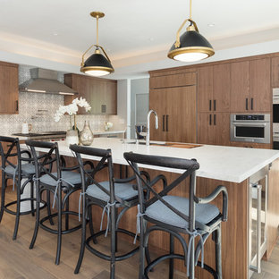 Transitional kitchen appliance - Kitchen - transitional medium tone wood floor kitchen idea in Los Angeles with an undermount sink, flat-panel cabinets, medium tone wood cabinets, multicolored backsplash, paneled appliances, an island and white countertops