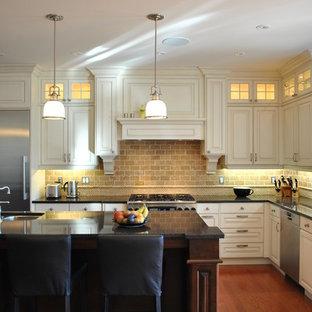 Inspiration för klassiska l-kök, med luckor med upphöjd panel, rostfria vitvaror, vita skåp och stänkskydd i travertin
