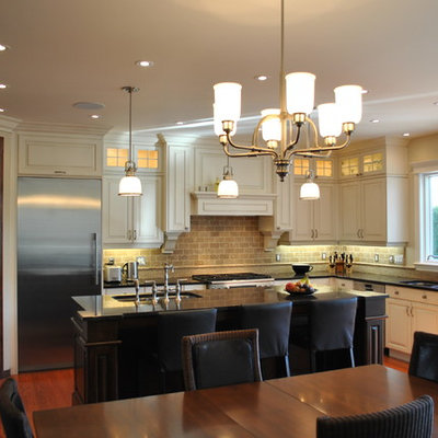 Elegant eat-in kitchen photo in Ottawa with raised-panel cabinets, white cabinets, stainless steel appliances and travertine backsplash