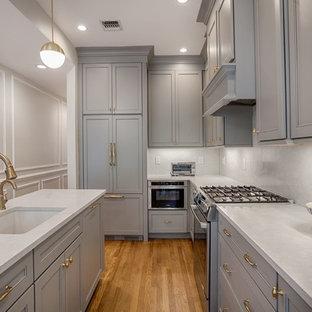 ニューヨークの小さいトランジショナルスタイルのおしゃれなキッチン (落し込みパネル扉のキャビネット、グレーのキャビネット、白いキッチンパネル、シルバーの調理設備、無垢フローリング、アンダーカウンターシンク、珪岩カウンター、石スラブのキッチンパネル、ベージュの床、白いキッチンカウンター) の写真