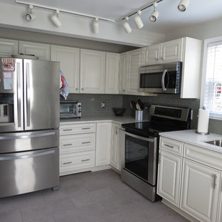 Mid-sized transitional eat-in kitchen designs - Example of a mid-sized transitional l-shaped purple floor eat-in kitchen design with an undermount sink, raised-panel cabinets, white cabinets, quartz countertops, gray backsplash, glass tile backsplash, stainless steel appliances, no island and white countertops