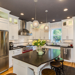 Inspiration for a timeless l-shaped medium tone wood floor kitchen remodel in Columbus with an undermount sink, shaker cabinets, white cabinets, white backsplash, subway tile backsplash, stainless steel appliances and an island