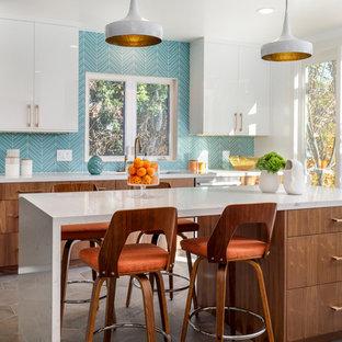 Пример оригинального дизайна: большая отдельная, п-образная кухня в стиле ретро с врезной раковиной, плоскими фасадами, синим фартуком, техникой из нержавеющей стали, островом, серым полом, фасадами цвета дерева среднего тона, столешницей из кварцита, фартуком из стеклянной плитки и полом из цементной плитки