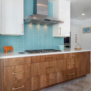 Geschlossene, Große Retro Küche in U-Form mit Unterbauwaschbecken, flächenbündigen Schrankfronten, hellbraunen Holzschränken, Quarzit-Arbeitsplatte, Küchenrückwand in Blau, Rückwand aus Glasfliesen, Küchengeräten aus Edelstahl, Zementfliesen, Kücheninsel und grauem Boden in Los Angeles