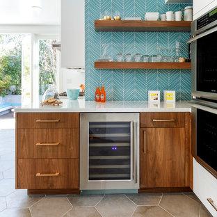 Cette image montre une grand cuisine vintage en U avec un évier encastré, un placard à porte plane, des portes de placard en bois brun, un plan de travail en quartz, une crédence bleue, une crédence en carreau de verre, un électroménager en acier inoxydable, un sol en carreaux de ciment, un îlot central et un sol gris.