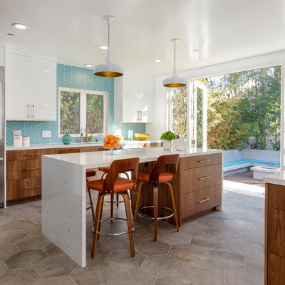 Large mid-century modern u-shaped cement tile floor and gray floor enclosed kitchen photo in Los Angeles with an undermount sink, flat-panel cabinets, medium tone wood cabinets, quartzite countertops, blue backsplash, glass tile backsplash, stainless steel appliances and an island