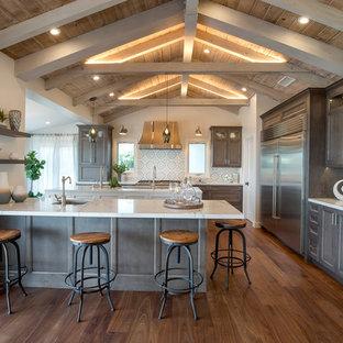 Foto på ett stort lantligt kök, med en undermonterad diskho, luckor med infälld panel, skåp i mörkt trä, bänkskiva i kvartsit, flerfärgad stänkskydd, stänkskydd i cementkakel, rostfria vitvaror, mellanmörkt trägolv, en köksö och brunt golv