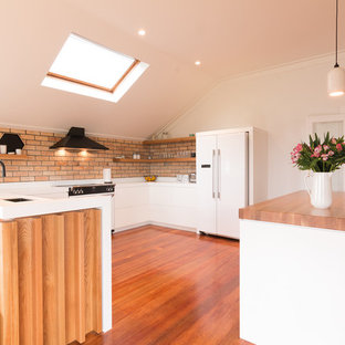 This is an example of a contemporary u-shaped kitchen in Melbourne with an undermount sink, flat-panel cabinets, white cabinets, medium hardwood floors, with island, brown floor and white benchtop.