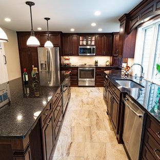 Geräumige Küche in L-Form mit Waschbecken, profilierten Schrankfronten, braunen Schränken, Granit-Arbeitsplatte, Küchenrückwand in Beige, Rückwand aus Travertin, Küchengeräten aus Edelstahl, Porzellan-Bodenfliesen, Kücheninsel, beigem Boden und schwarzer Arbeitsplatte in Philadelphia