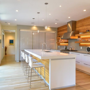 Modern kitchen designs - Minimalist l-shaped light wood floor and beige floor kitchen photo in Los Angeles with an undermount sink, flat-panel cabinets, white cabinets, gray backsplash, stainless steel appliances, an island and gray countertops