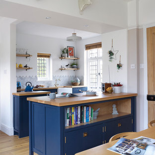 Classic u-shaped kitchen/diner in Other with a belfast sink, shaker cabinets, blue cabinets, wood worktops, marble splashback, integrated appliances, light hardwood flooring, grey splashback, a breakfast bar, brown floors and brown worktops.