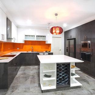 Große Moderne Wohnküche in U-Form mit Doppelwaschbecken, grauen Schränken, Mineralwerkstoff-Arbeitsplatte, Küchenrückwand in Orange, Glasrückwand, Küchengeräten aus Edelstahl, Porzellan-Bodenfliesen und Kücheninsel in Darwin