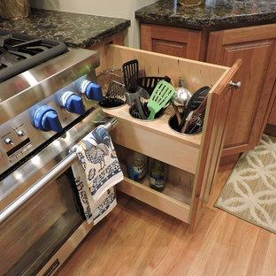 Exempel på ett klassiskt kök, med luckor med upphöjd panel, bruna skåp, ljust trägolv och beiget golv