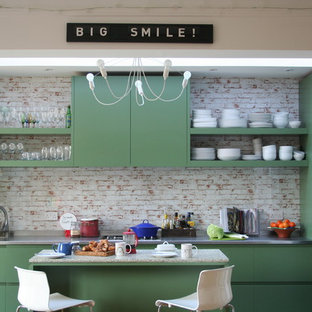 This is an example of a mid-sized transitional eat-in kitchen in London with flat-panel cabinets, green cabinets, an integrated sink, stainless steel benchtops, multi-coloured splashback, stainless steel appliances and with island.