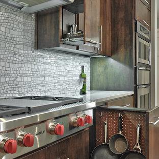 Photo of a mid-sized contemporary single-wall kitchen in Austin with flat-panel cabinets, mosaic tile splashback, stainless steel appliances, quartz benchtops, grey splashback, medium hardwood floors and dark wood cabinets.