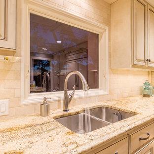 Große Klassische Wohnküche in U-Form mit Unterbauwaschbecken, profilierten Schrankfronten, beigen Schränken, Granit-Arbeitsplatte, Küchenrückwand in Beige, Rückwand aus Steinfliesen, Elektrogeräten mit Frontblende, braunem Holzboden und Kücheninsel in Austin