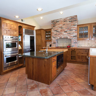 Farmhouse kitchen ideas - Example of a country u-shaped terra-cotta floor and red floor kitchen design in DC Metro with a double-bowl sink, glass-front cabinets, medium tone wood cabinets, beige backsplash, stainless steel appliances, an island and white countertops