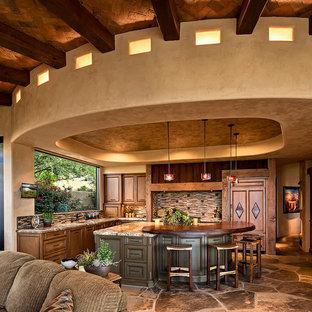 フェニックスの広いサンタフェスタイルのおしゃれなキッチン (シェーカースタイル扉のキャビネット、中間色木目調キャビネット、御影石カウンター、茶色いキッチンパネル、ボーダータイルのキッチンパネル、ベージュの床) の写真