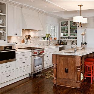 Imagen de cocina en L, clásica, con armarios tipo vitrina, electrodomésticos de acero inoxidable y salpicadero de piedra caliza