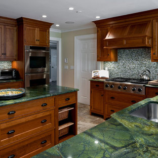 This is an example of a traditional kitchen in New York with mosaic tile splashback, stainless steel appliances, an undermount sink, recessed-panel cabinets, dark wood cabinets and green benchtop.