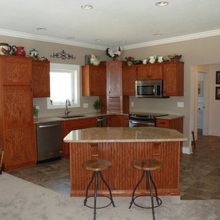 Photo of a mid-sized traditional l-shaped separate kitchen in Grand Rapids with an undermount sink, louvered cabinets, dark wood cabinets, laminate benchtops, stainless steel appliances, porcelain floors and with island.