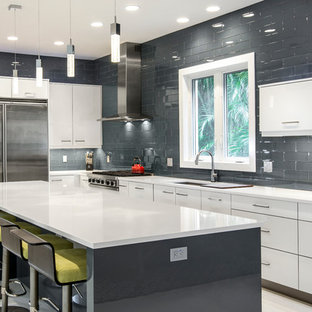 Contemporary eat-in kitchen ideas - Inspiration for a contemporary l-shaped porcelain tile eat-in kitchen remodel in Miami with gray backsplash, glass tile backsplash, stainless steel appliances, flat-panel cabinets, white cabinets, an undermount sink, an island and solid surface countertops
