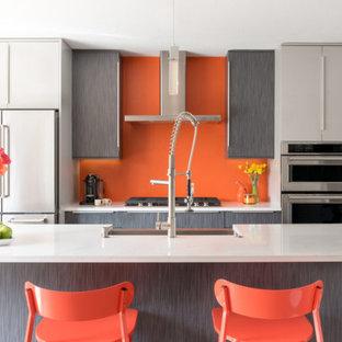 デンバーのコンテンポラリースタイルのおしゃれなキッチン (エプロンフロントシンク、フラットパネル扉のキャビネット、グレーのキャビネット、オレンジのキッチンパネル、シルバーの調理設備の、白いキッチンカウンター) の写真