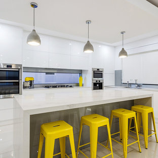 Contemporary kitchen in Hobart with flat-panel cabinets, white cabinets, stainless steel appliances and an island.