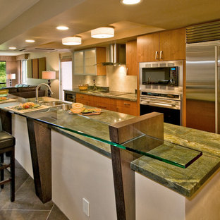 Design ideas for a large tropical l-shaped kitchen in Hawaii with an undermount sink, flat-panel cabinets, medium wood cabinets, granite benchtops, beige splashback, stone tile splashback, stainless steel appliances, slate floors, with island, grey floor and green benchtop.